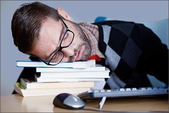 Mann mit Brille ist müde und schläft an seinem Schreibtisch