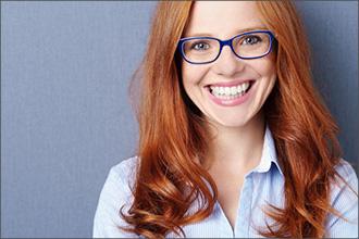 Rothaarige Frau trägt Brille