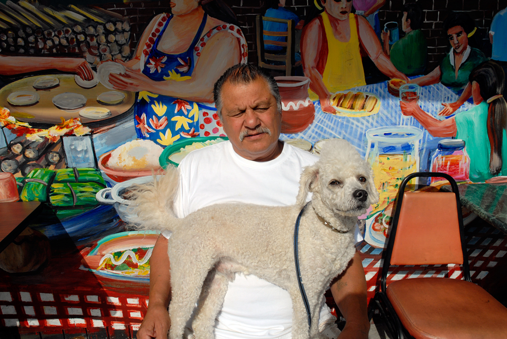 A man and his dog at the Paraiso Cafe in the Mission