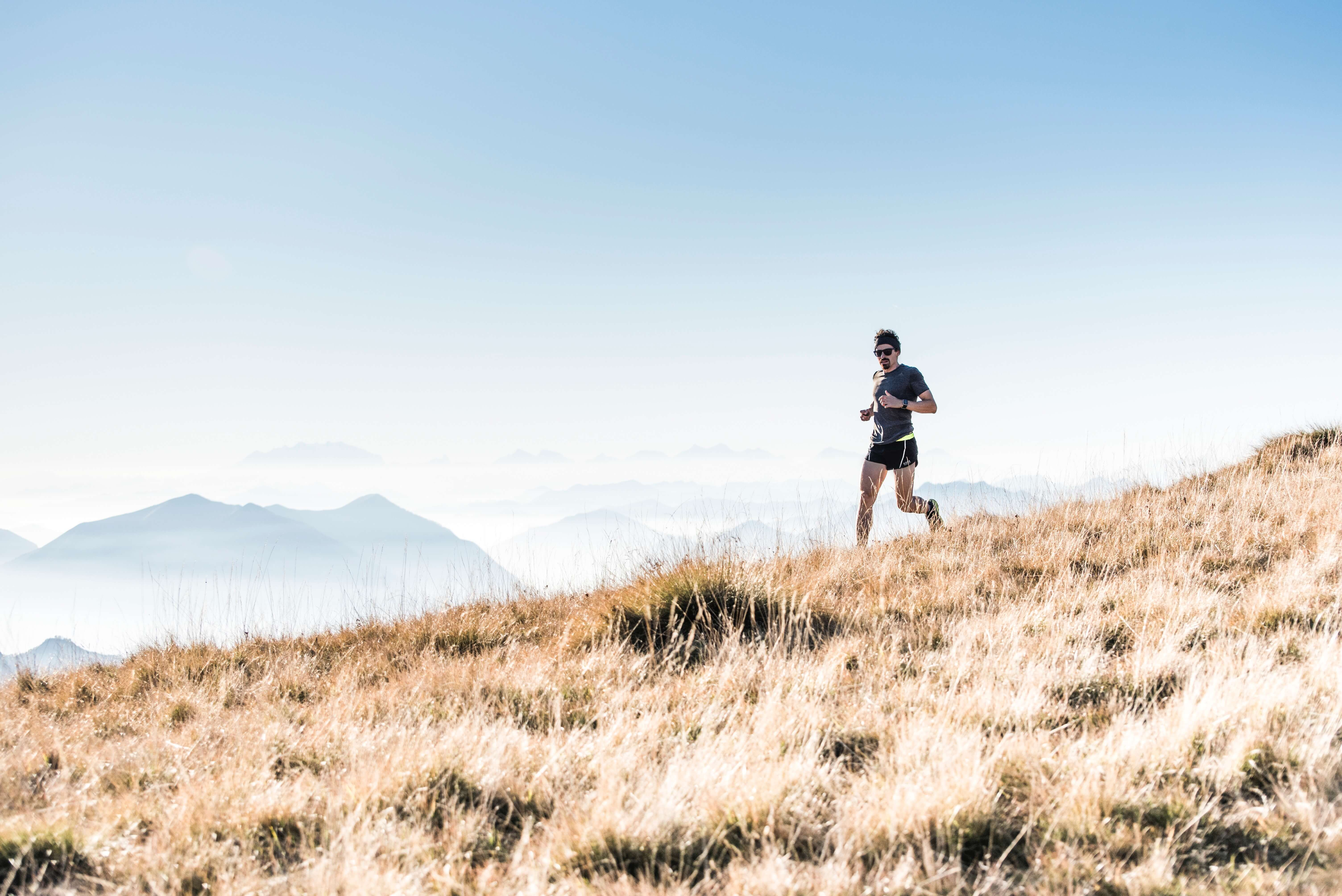 Image shows man running across a field with mountains in the distance. Representing frugal exercise.