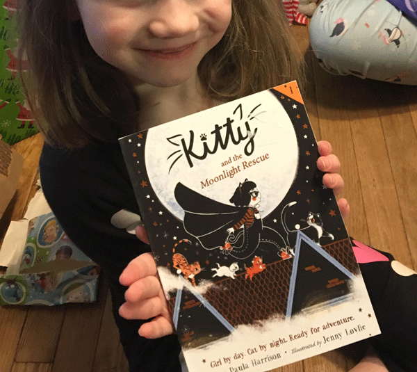 "image of Miss M (pictured mid face down) holding the book ""Kitty and the Moonlight Rescue"" with a big grin on her face"