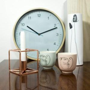 Niebieski okrągły zegar ścienny, miedziany świecznik i kubeczki z myszką