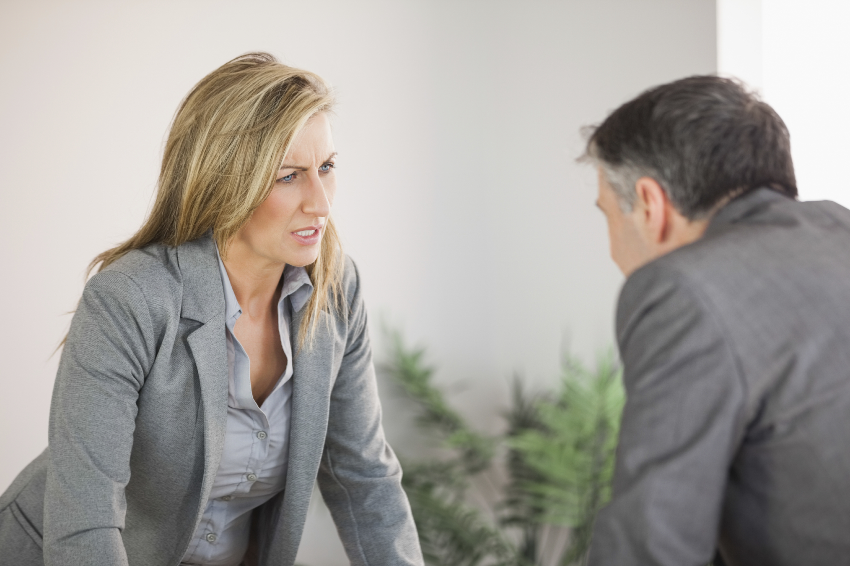 A blonde businesswoman getting angry with a businessman