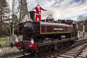 Santa standing on top of the train