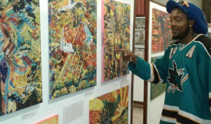 Dominican artist, Shadrach Burton speaking about his artwork during the Caribbean Fine Art Fair (CaFA).