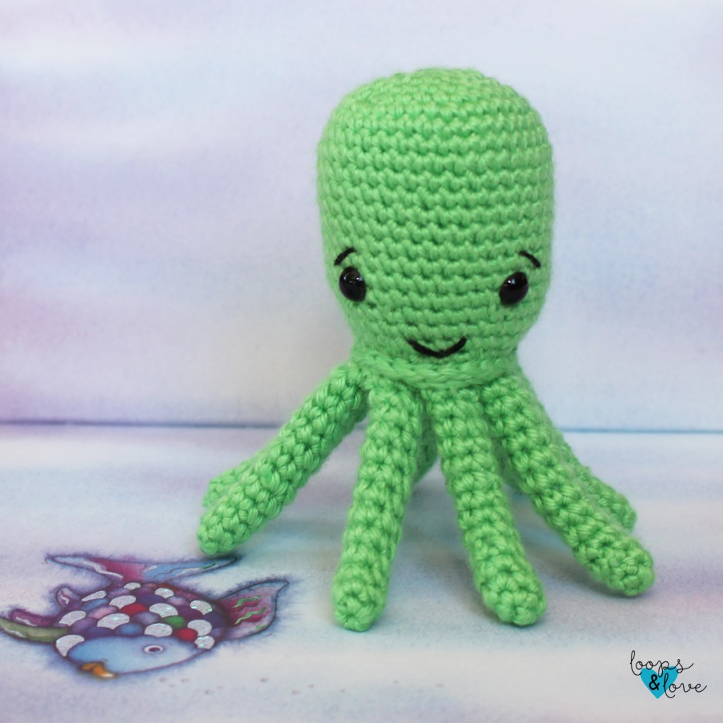 Crochet octopus sitting on a blue blackground