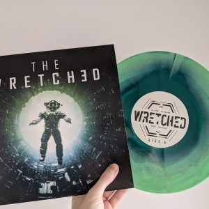 A hand holds a vinyl record against a white background. The record is sticking out of its sleeve. The sleeve shows an astronaut falling backwards into a glowing white void, with the title THE WRETCHED above them. The record itself is marble with two different shades of green. The label holds a sci-fi logo that reads THE WRETCHED.