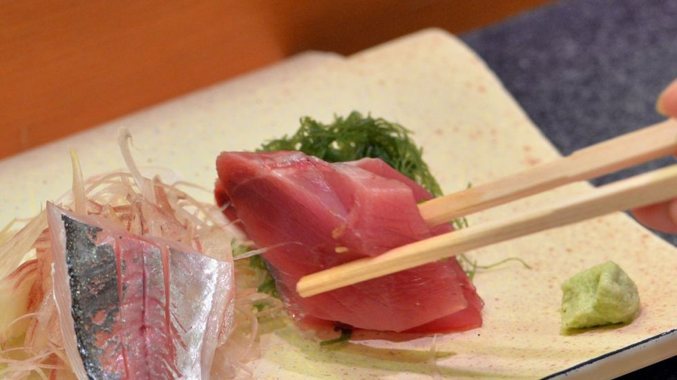 Comer pescado mejora la salud del cerebro - This photo taken on July 16, 2013 shows a customer eating bonito and horse mackerel sashimi (raw fish) at a high-end sushi restaurant in Tokyo.  There is no menu and the chef selects the best fish available for customers, which costs at least 10,000 yen (100 USD) per person. While high-end restaurants cater to regular clientËle, many traditional sushi restaurants - a business steeped in tradition - nowadays must compete with