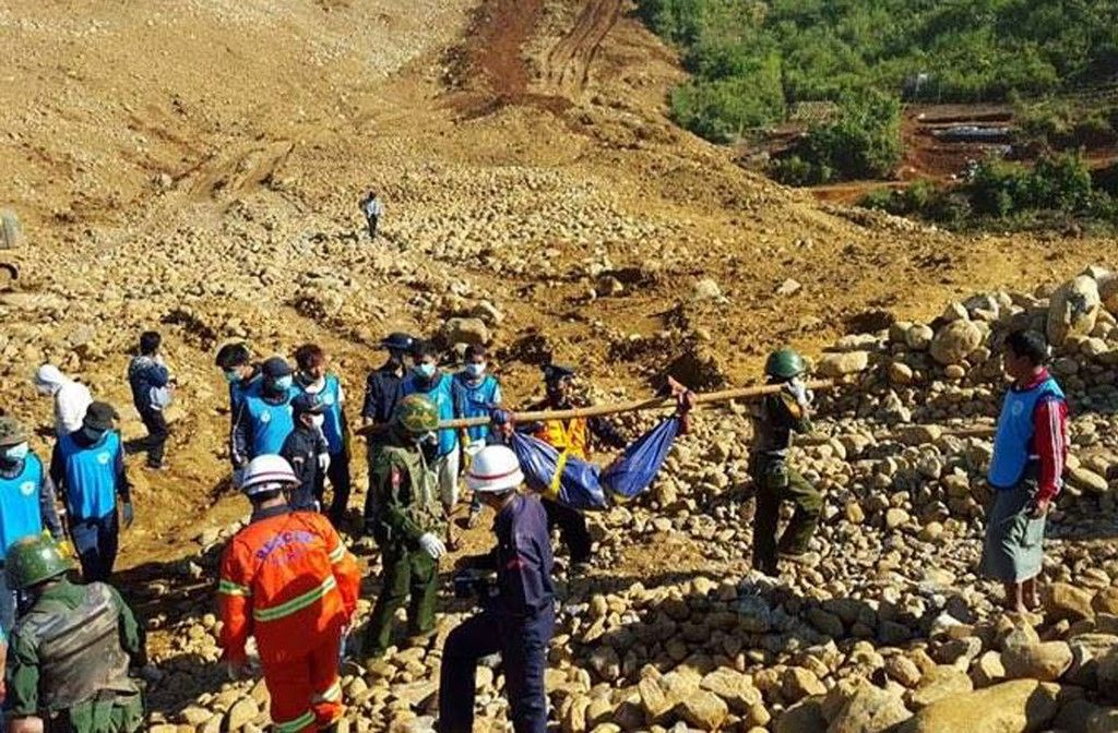 Soldiers carry the bodies of miners killed by a landslide in a jade mining area in Hpakhant, in Myanmar's Kachin state on November 22, 2015. At least 90 people have died in a huge landslide in a remote jade mining area of northern Myanmar, officials said on November 22, as search teams continued to find bodies in one of the deadliest disasters to strike the country's shadowy jade industry.  AFP PHOTO / AFP / STR