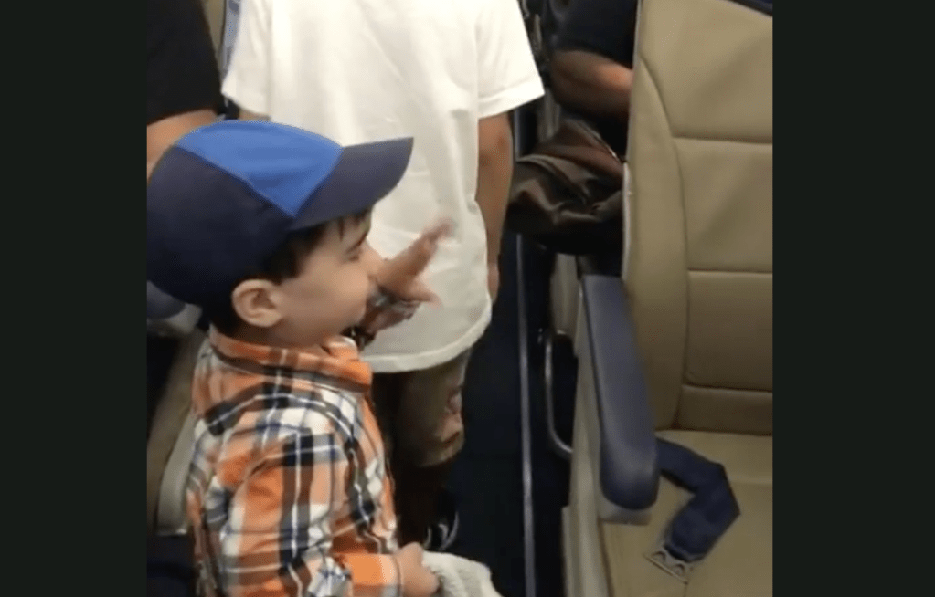 #VIRAL Niño de dos años saluda a pasajeros en pasillo de avión - Captura de pantalla