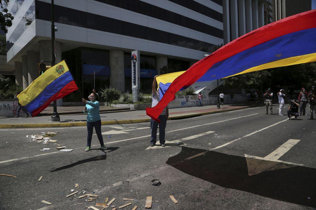 ¿Elecciones regionales para qué? - Manifestantes ondean una bandera de Venezuela durante una protesta contra el gobierno del presidente Nicolás Maduro en Caracas, el 8 de agosto de 2017. EEUU anunció el miércoles 9 de agosto nuevas sanciones a ocho personas más en Venezuela, incluyendo al hermano del fallecido presidente Hugo Chávez. (AP Foto/Wil Riera)