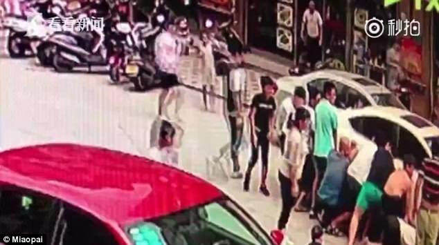 #Video Multitud levanta automóvil para rescatar a niño - Foto de Daily Mail
