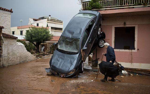 Inundaciones en Atenas dejan al menos 19 muertos - Un hombre pasa por una carro arrastrado por corrientes de barro causadas por una inundación en la ciudad de Mandra, en la periferia occidental de Atena, en Grecia, el jueves 16 de noviembre del 2017. (AP Foto/Petros Giannakouris)