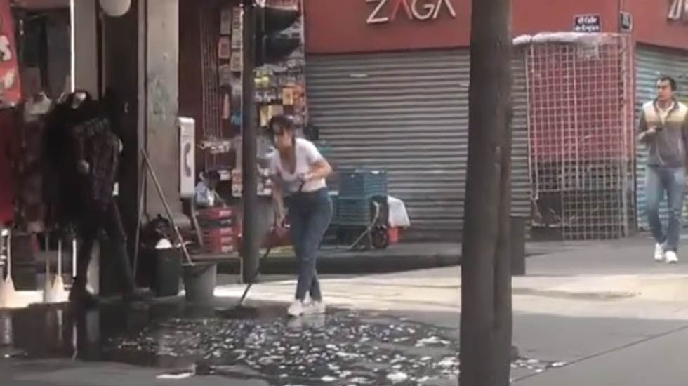 Comerciantes capitalinos viven sin contratiempos corte de agua - Comerciantes asean con cubetas de aguas sus negocios. Captura de pantalla