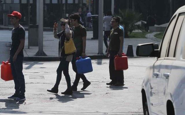 Recipientes para cargar gasolina serán desechados de manera especial - Gente cargando gasolina en bidones. Foto de Notimex