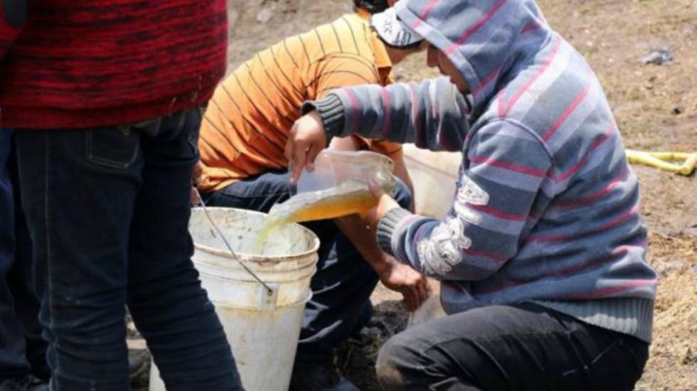 AMLO pide cambiar ley 'blanda' en materia de robo de hidrocarburos - Personas recolectando combustible. Foto de AFP