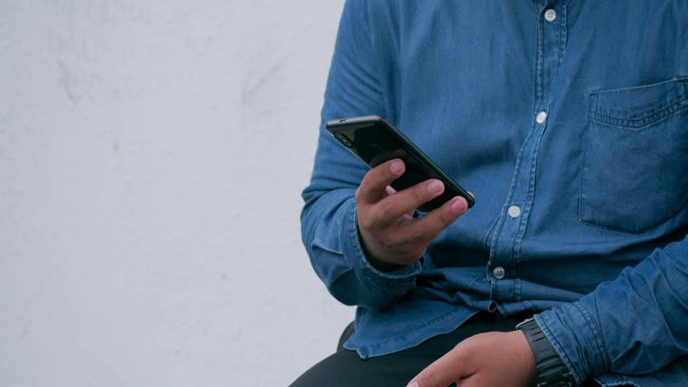 Persona con un teléfono. Foto de @utsmanmedia
