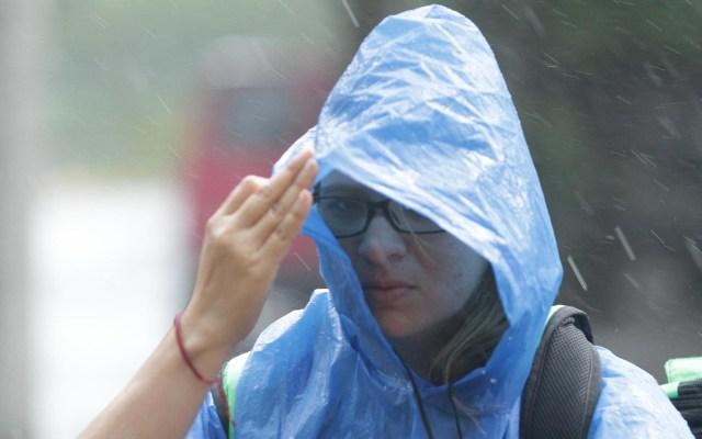 Pronostican lluvias generalizadas en todo el país - Mujer cubriéndose de la lluvia. Foto de Notimex