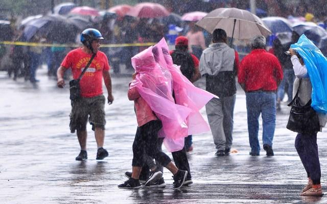 Alerta Amarilla por lluvias y granizo en la Ciudad de México - Gente cubriéndose de la lluvia en la Ciudad de México. Foto de Notimex