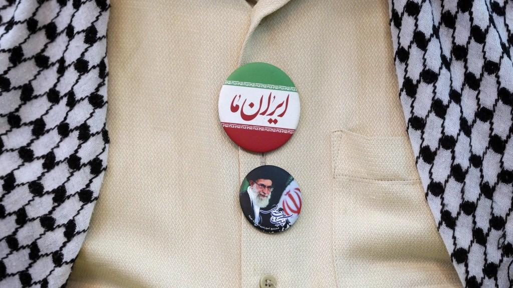 Trump niega que iraníes detenidos sean espías de la CIA - Un hombre iraní lleva una bufanda palestina ('keffiyeh') e insignias que representan al líder supremo iraní Ayatollah Ali Khamenei y la bandera nacional de Irán en su camisa. Foto de EFE / EPA / Abedin Taherkenareh