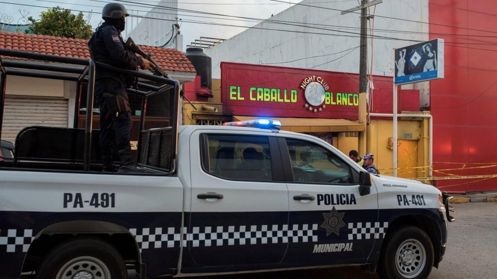 CJNG detrás de la masacre en bar de Coatzacoalcos: SSP de Veracruz - Agentes de la policía pasan  frente al bar El Caballo Blanco, atacado por un grupo armado, en Coatzacoalcos, Veracruz. Foto de EFE/ Ángel Hernández