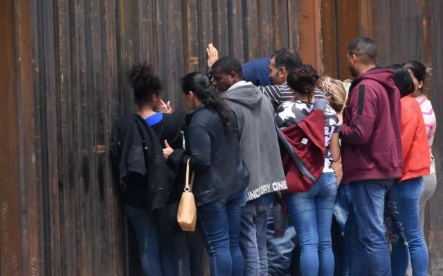 Bajan detenciones de indocumentados en frontera EE.UU.-México - Migrantes centroamericanos se asoman por el muro fronterizo de EE.UU. con México para entregarse. Foto de EFE