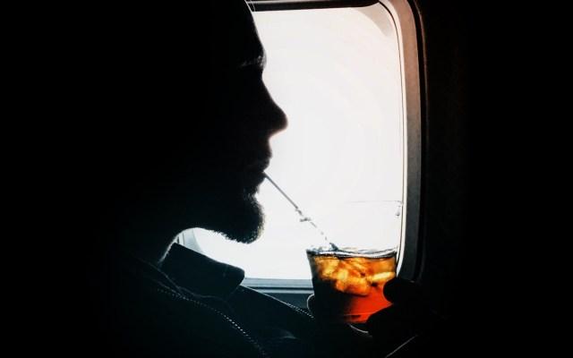 Los efectos del alcohol al viajar en avión - Pasajero de avión bebiendo. Foto de John Luke Laube / Unsplash