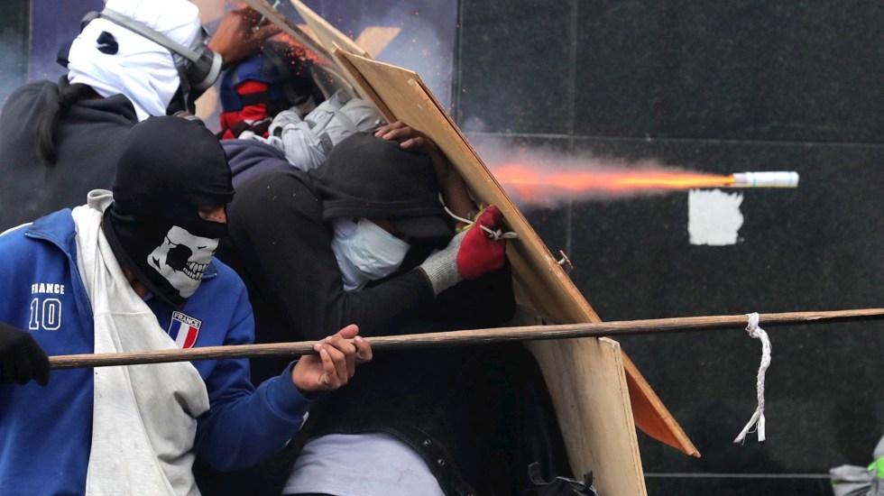 Con gases lacrimógenos, policía dispersa manifestación de indígenas en Quito - Manifestantes se enfrentan a la policía durante una nueva jornada de protestas con presencia indígena este viernes, en Quito (Foto de EFE/ Paolo Aguilar).