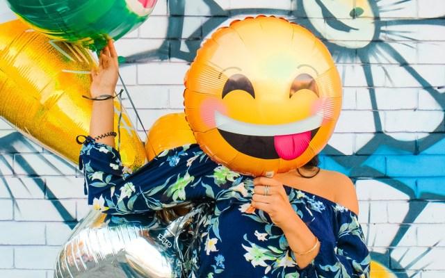 Fundéu BBVA elige a los emojis como palabra del año - Mujer se cubre la cara con globo de emoji. Foto de Lidya Nada / Unsplash