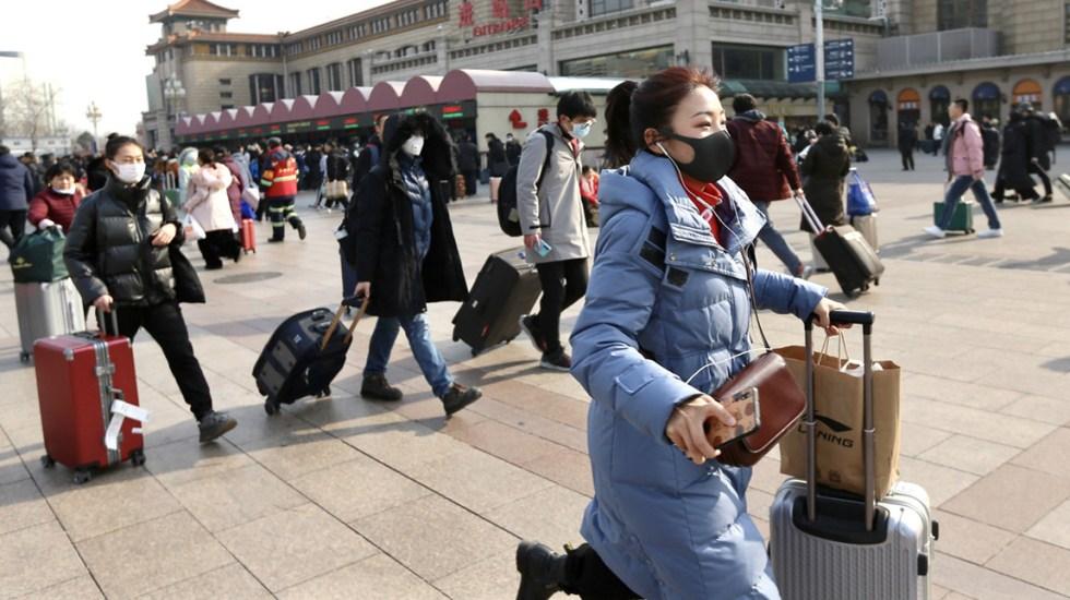 Suspenden vuelos en Wuhan para evitar propagación de nuevo coronavirus - Viajeros usan máscaras en estación de ferrocarril de Beijing, China. Foto de China Daily