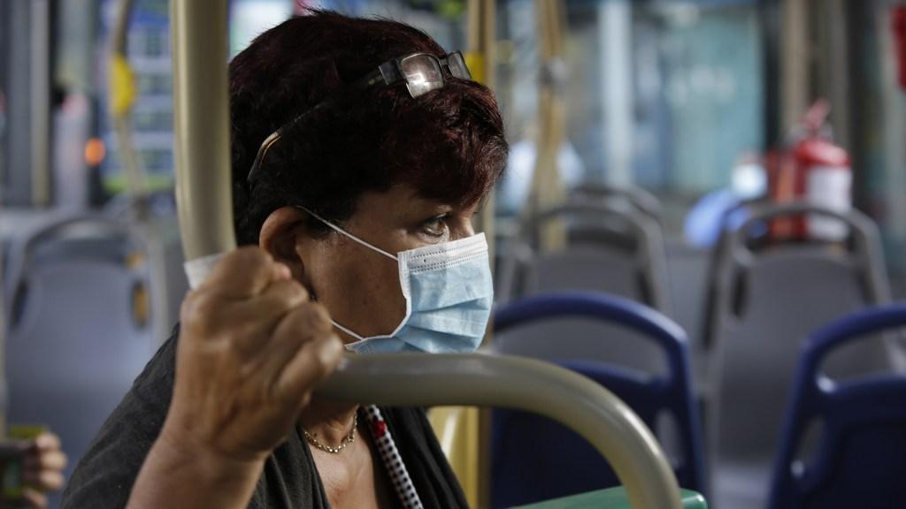 Panamá emite bonos por 2 mil millones de dólares ante crisis del COVID-19 - Mujer con cubrebocas para evitar el COVID-19 en transporte público de Panamá. Foto de EFE