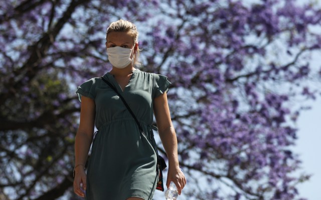 Tlaxcala confirma primer caso de COVID-19 - Una mujer con tapabocas camina por calles de la Ciudad de México durante el primer día de la Jornada Nacional de Sana Distancia. Foto de EFE