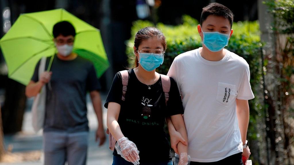 Suman 3 mil 200 muertos por COVID-19 en todo el mundo - Personas asiáticas salen a la calle con cubrebocas y guantes para evitar el COVID-19. Foto de EFE