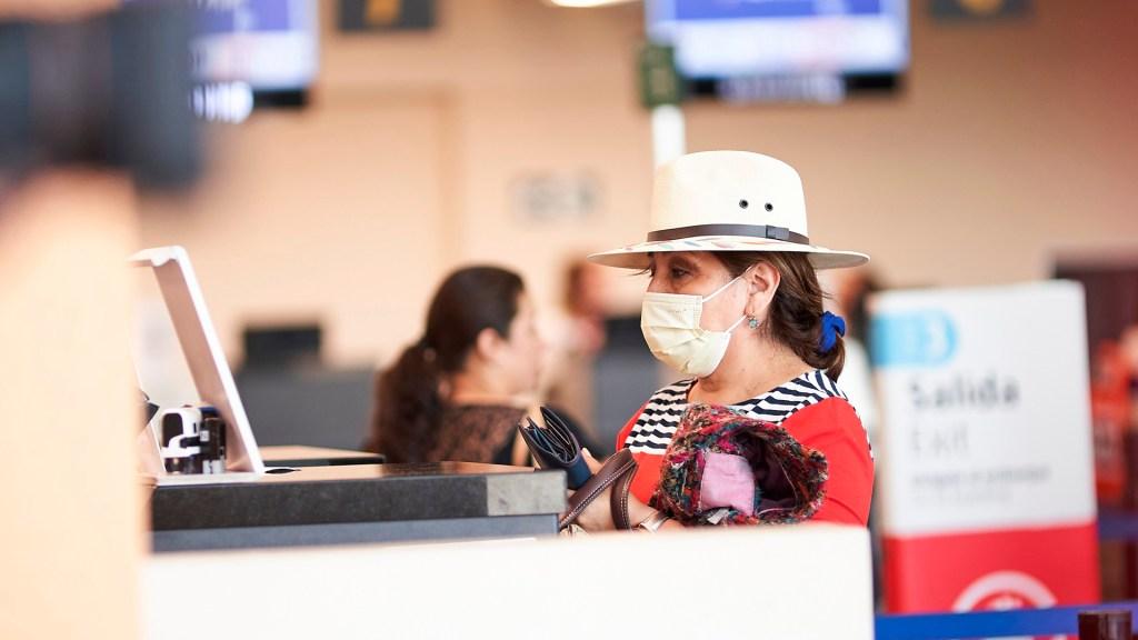 EE.UU. podría restringir viajes a Europa por el coronavirus - Viajera extrema precauciones en aeropuerto por el COVID-19. Foto de EFE
