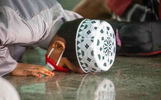 Celebraciones de Eid al-Fitr en Bangladesh - Un joven musulmán protegido con una máscara facial asiste al rezo del Eid al-Fitr en la Mezquita Nacional de Baitul Mukarram en Dhaka, Bangladesh. Foto de EFE/ EPA/ MONIRUL ALAM.