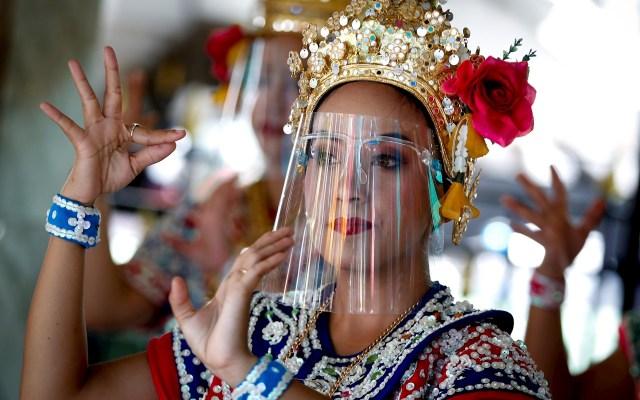 Coronavirus en Tailandia - Bailarinas ataviadas con máscaras protectoras actúan este jueves en el templo de Erawan, en Bangkok, Tailandia. El país ha alargado el estado de emergencia hasta el final de junio para frenar la propagación de la pandemia del coronavirus. Foto de EFE/ Diego Azubel.