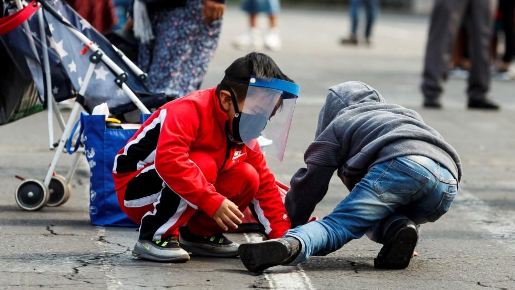 Acusa Redim al Gobierno Federal de 'abandonar' a 40 millones de niños durante pandemia - Niño juega con otro, con careta protectora y cubrebocas para evitar el COVID-19, en la Ciudad de México. Foto de EFE
