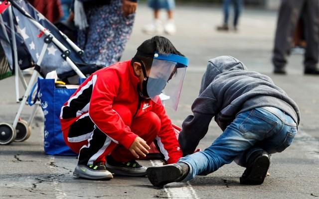 Estudio revela nuevos detalles sobre complicaciones de COVID-19 en niños - Niño juega con otro, con careta protectora y cubrebocas para evitar el COVID-19, en la Ciudad de México. Foto de EFE