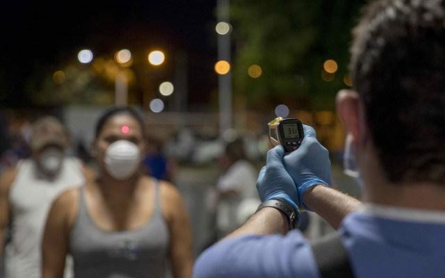 Anciano muere en la fila para recibir pensión en Nicaragua - Un doctor toma la temperatura a una mujer como medida de prevención ante el coronavirus, durante una velada de boxeo en Managua. Foto de EFE