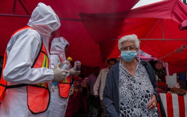 Reanudarán operativos para evitar venta de medicamentos robados en tianguis de la Ciudad de México - Personal sanitario ofrece gel antibacterial en la entrada de un tianguis de Iztapalapa. Foto de Notimex