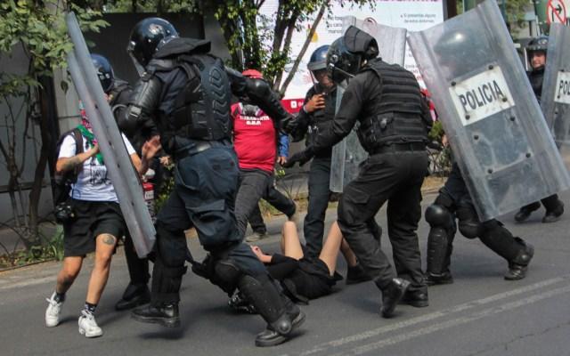 Detienen a policías que patearon a joven durante protesta en CDMX - Foto de Notimex