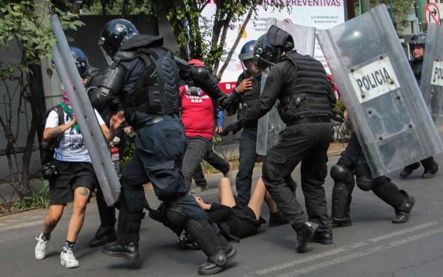Vinculan a proceso a policías implicados en agresión contra encapuchada en Polanco - Policías rodean a joven agredida por al menos dos oficiales durante las protestas del 5 de junio en la Ciudad de México. Foto de Notimex