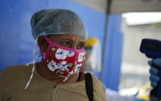 El Salvador levanta cuarentena por COVID-19 tras fallo constitucional - Toma de temperatura a mujer para detectar COVID-19, en El Salvador. Foto de EFE