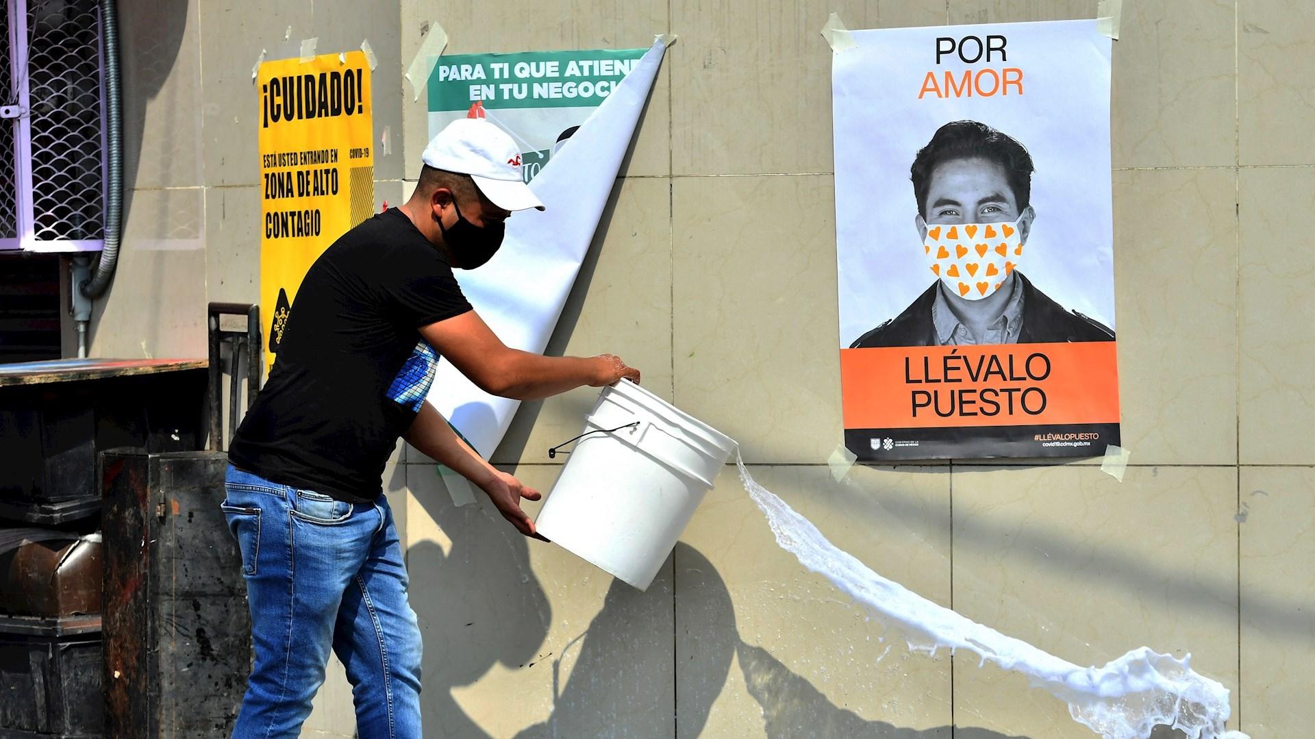 Habitantes de una colonia en Ciudad de México se dan a la tarea de desinfectar sus calles señaladas como de alto riesgo de contagio del COVID-19. Foto de EFE/Jorge Núñez