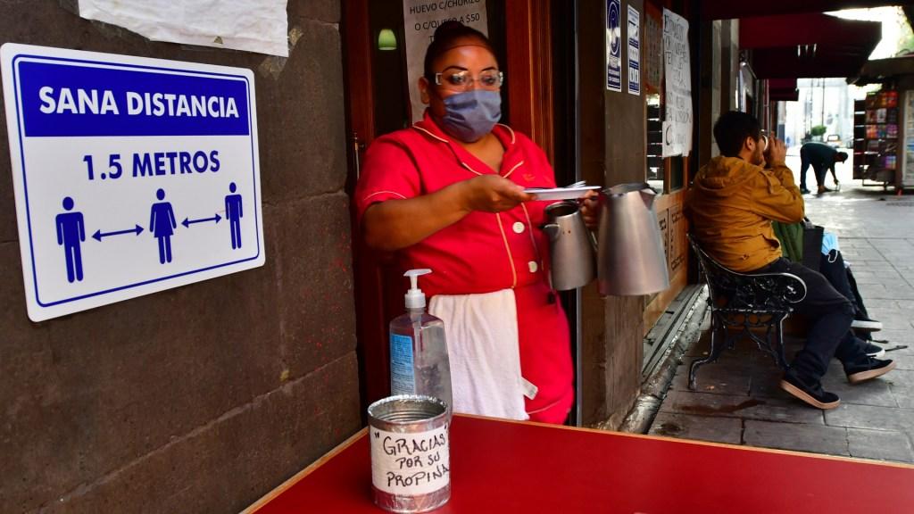En septiembre se generaron 113 mil 850 empleos, confirma IMSS; siguen sin trabajo 719 mil 250 - Empleada en la entrada de una cafetería en el Centro Histórico de la Ciudad de México. Foto de EFE