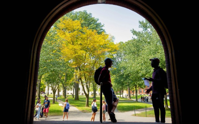 Universidades de EE.UU. refuerzan lucha contra norma para visas de estudiantes - Estudiantes de Harvard bajo del arco Sever Hall. Foto de Harvard Unyversity