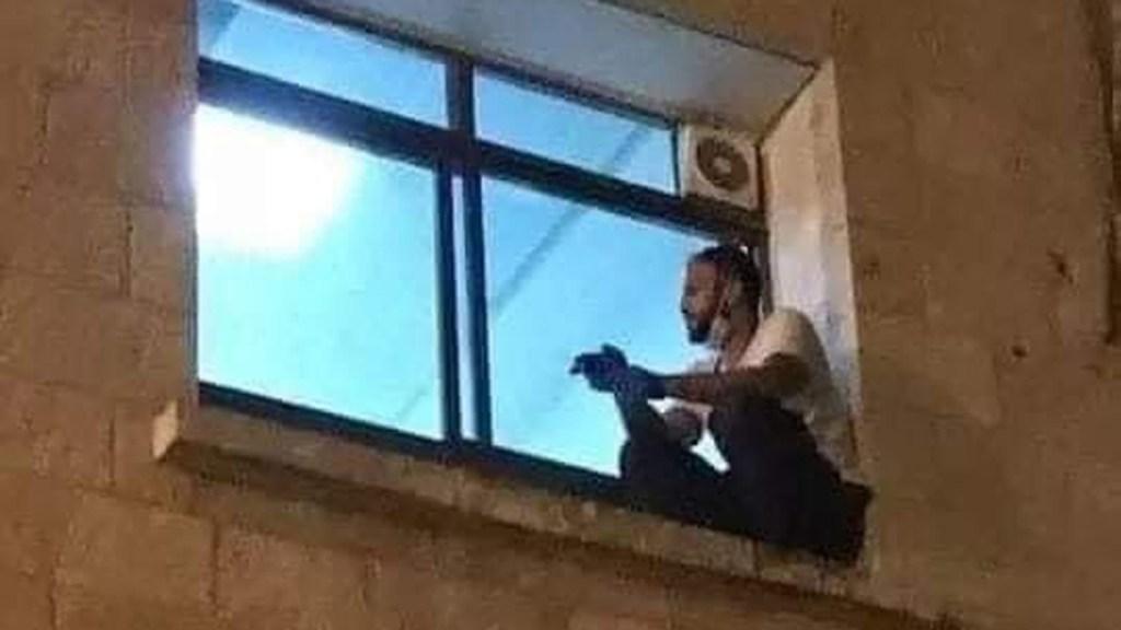 Joven trepó ventana de hospital para ver a su madre antes de morir por COVID-19 - Jihad Al-Suwaiti en ventana del cuarto de hospital de su madre antes de morir por COVID-19. Foto de @mhdksafa