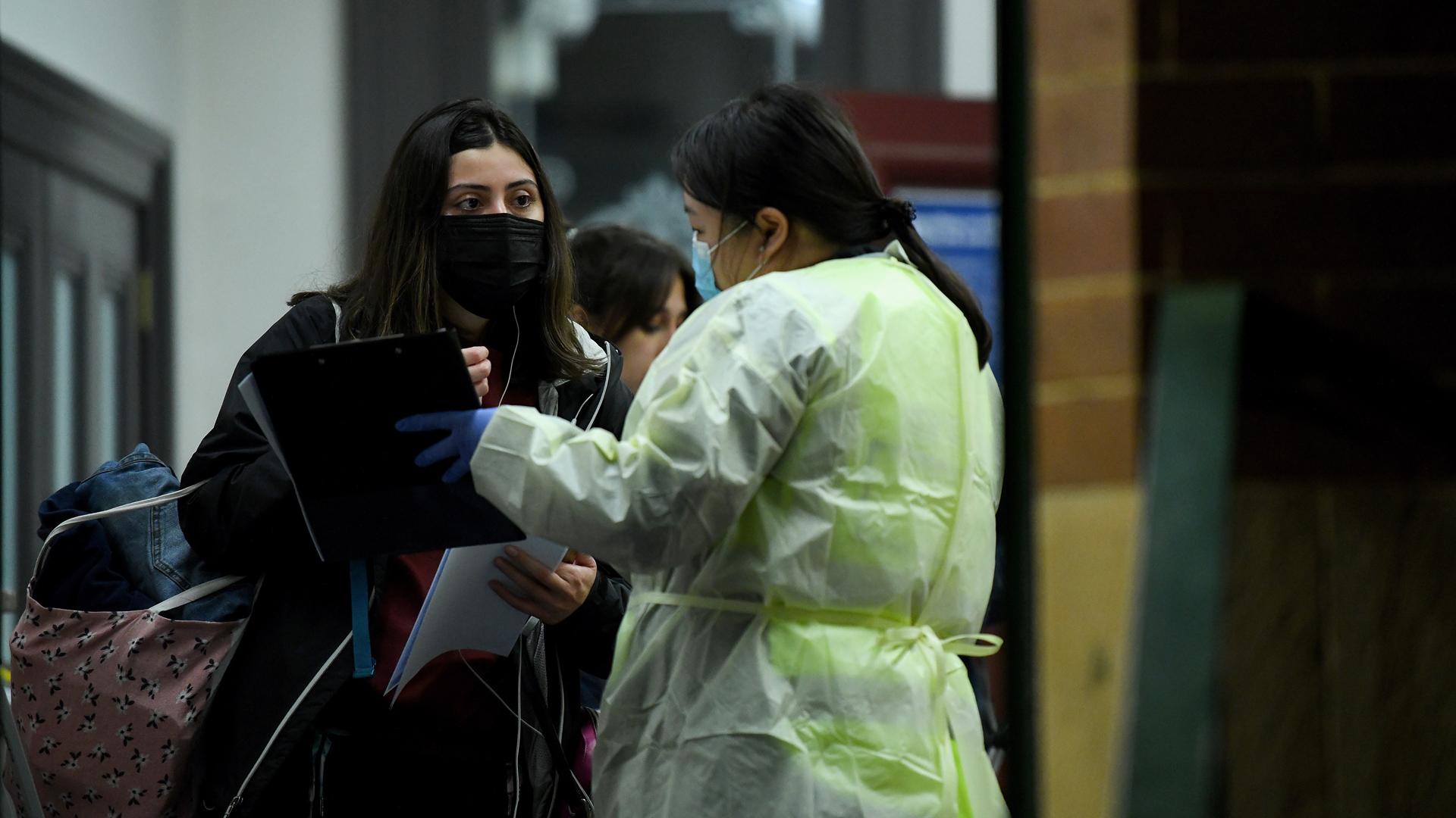 Diez mil australianos rechazan prueba de COVID-19 por teorías de conspiración- Personal sanitario de Australia habla con viajeros recién llegados a Sidney provenientes de Melbourne sobre las restricciones por COVID-19