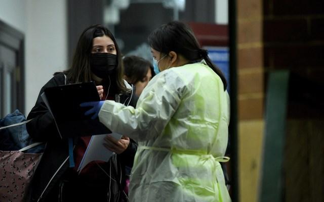 Diez mil australianos rechazan prueba de COVID-19 por teorías de conspiración - Personal sanitario de Australia habla con viajeros recién llegados a Sidney, provenientes de Melbourne, sobre las restricciones por COVID-19. Foto de EFE
