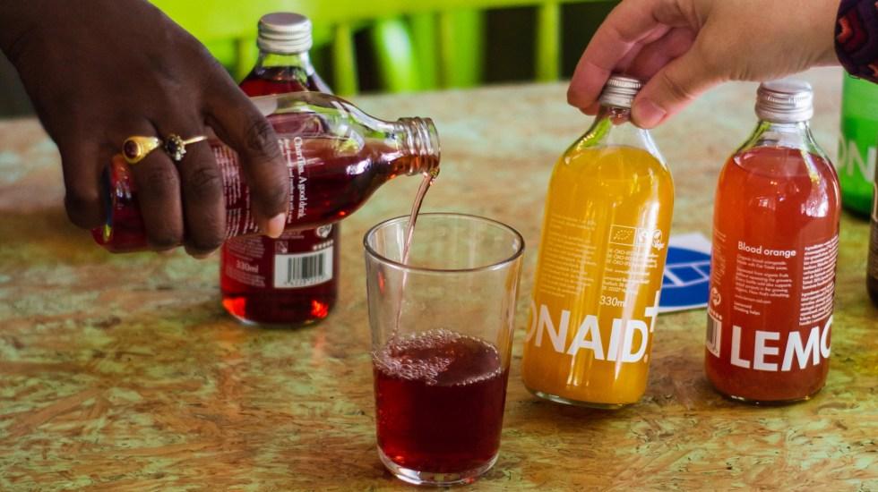Expertos urgen a regular bebidas azucaradas para evitar muertes en México - Personas sirven refresco en vasos. Foto de Louis Hansel / Unsplash